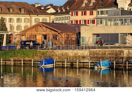 Rapperswil, Switzerland - 30 November, 2016: boats at the emabnkment of Lake Zurich, people and buildings on Fischmarktplatz square at sunset. Rapperswil is a part of the municipality of Rapperswil-Jona in the Swiss Canton of St. Gallen.