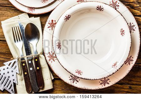 Christmas table setting. Plates, spoon fork knife, Christmas decoration on wooden background. Christmas background. Top view