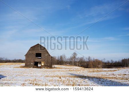 An abandoned barn and hayloft in an agricultural rural winter landscape