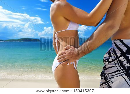 Happy couple standing arm in arm on the beach on the shore of a tropical island background. Philippines