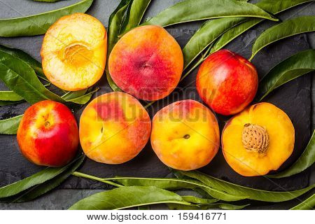 Fresh peaches with fresh leaves on black stone slate plate on gray stone slate background. Summer peaches top view
