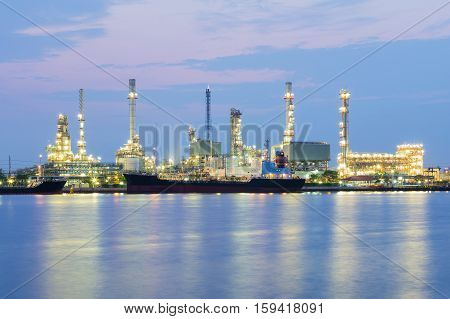 Oil factory river side at night, heavy industrial manufacturing background