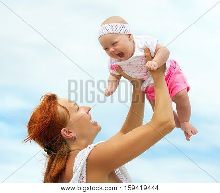 Beautiful Mother And Baby outdoors. Nature. Beauty Mum and her Child playing in beach together. Outdoor Portrait of happy family. Joy. Mom and Baby