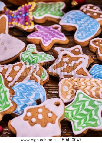 Christmas background multicolored gingerbread cookies and cinnamon sticks on woden table .
