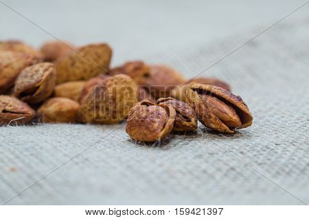Almond nut in shell and shelled close up. Placed on the sack. Focus on almonds. Background blur out of focus