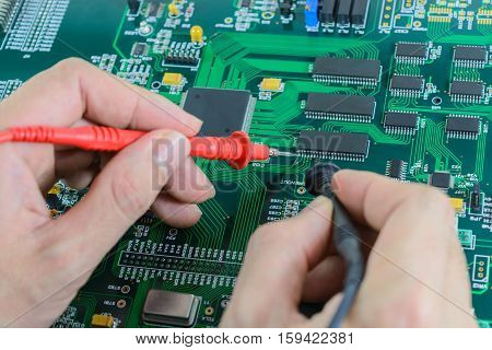Multimeter test probes on printed circuit board