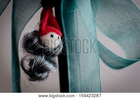 Christmas toy Santa Claus head made of cloth hanging on a bow