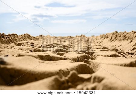 Traces of the big wheel tread on the sand on a sky background
