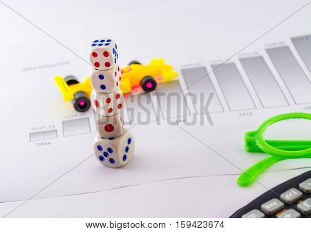 business and market profit ,loss  analyzing table photograph with stack of dices,one formula car toy,1 growing histogram,1 toy glasses and a calculator