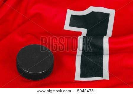 Washer and red ice hockey jersey with the number one. Texture background hockey