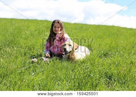 beautiful young girl and dog lying on green meadow