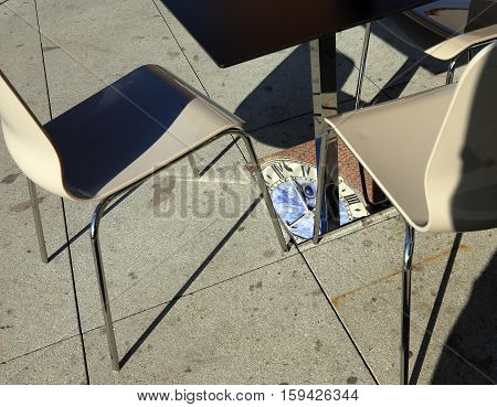 reflection of the ancient clock tower on the leg of a table of an Italian alfresco cafe
