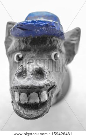 Statuette of a donkey's head in a blue cap close up on a white background.