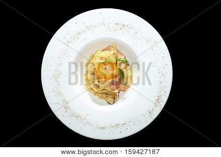 Spaghetti carbonara with egg yolk on black background