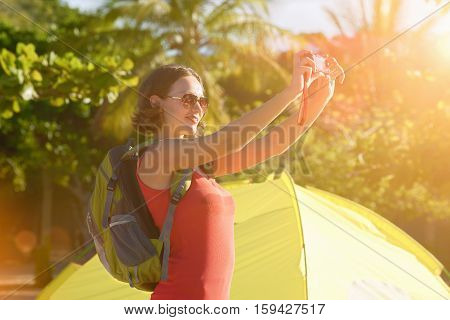 Portrait of happy backpacker girl with photo camera enjoying sunrise view. Travel to Asia happiness emotion summer holiday concept