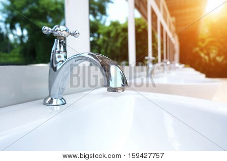 Water drop from chrome faucet and water pipeline sepia tone background. Wash Basin ceramic tile at bathroom. Drink water plumbing pipeline. Resource conserve concept.
