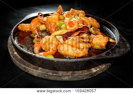 Spicy fried seafood on hot pan with black background