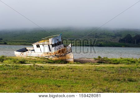 rusty old ship on the shore of river