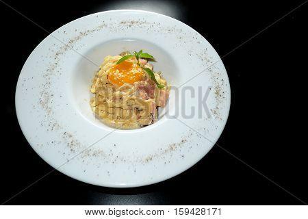 Spaghetti carbonara with egg yolk on black background