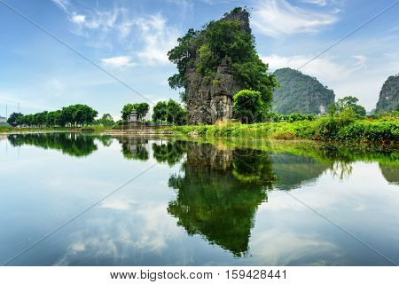 Scenic natural karst tower reflected in water of the Ngo Dong River at the Tam Coc portion Ninh Binh Province Vietnam. The Tam Coc is a popular tourist attraction in Asia.