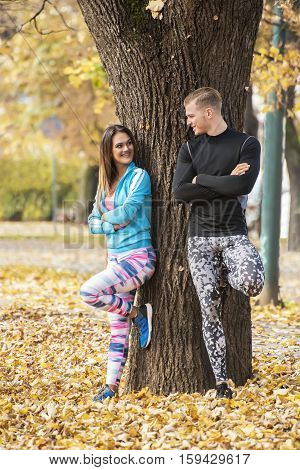 Beautiful Young Couple Recumbent To Tree Together In The Park. Autumn Environment.