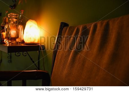 A low key photo of an interior scene of an armchair besides a small table with a bottle of whiskey lit by a Himalayan salt lamp.