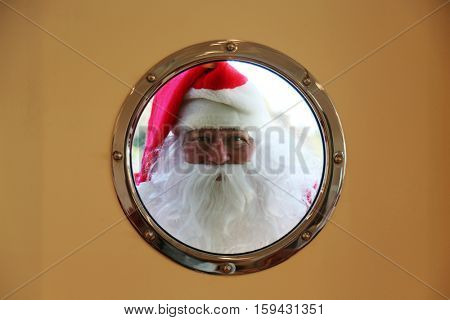 Santa Claus looks in a window or porthole from the outside to see if anyone is home. Cute Santa Claus concepts.