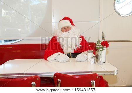 Santa Claus sits in a restaurant or diner. Cute Santa Claus concepts.