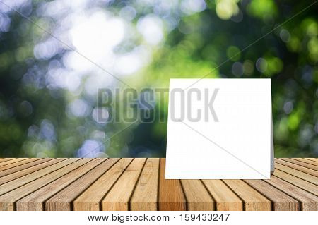 white card put on Wooden desk or wooden floor on green bokeh background.use for present or mock up your product.clipping path include
