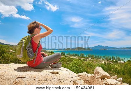 Young tourist with backpack think on top of the mountain and enjoying beatiful coast view. Ecotourism concept image with happy female hiker.