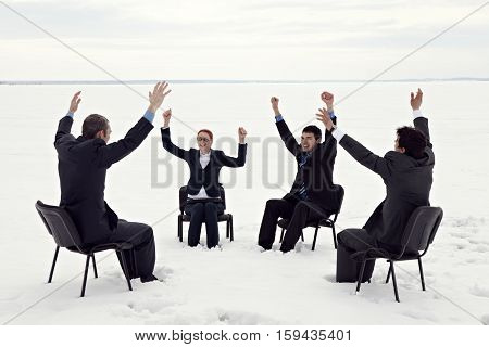 Excited business people with raised arms sitting outdoors in winter