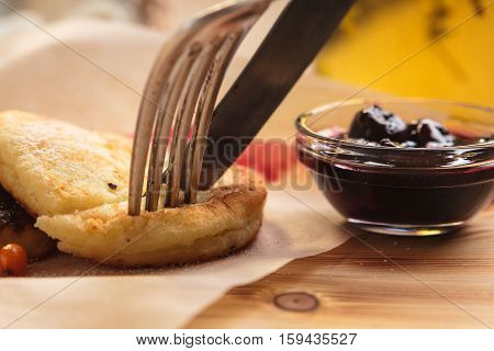 Cheese Pancakes Piece With Cherry Sauce On A Fork.