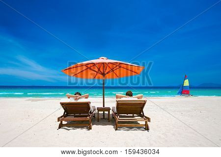 Couple on a tropical beach relax in the sun on deck chairs under a red umbrella. Travel background .