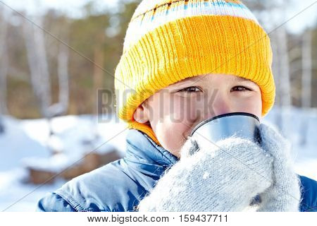Smiling boy drinking hot tea in cold winter day and looking at camera