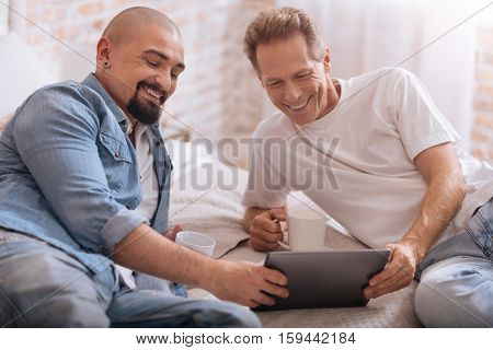 We having fun together. Smiling positive cheerful non-traditional couple lying on the bed and drinking tea while expressing happiness and watching videos on the tablet