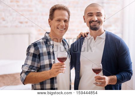 We enjoying our weekend. Smiling cheerful non-traditional couple standing in the bedroom and drinking wine while expressing happiness and hugging each other