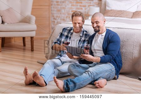 We enjoying our romantic atmosphere. Delighted positive non-traditional couple sitting on the floor in the bedroom and drinking wine while expressing love and care and looking videos on the tablet