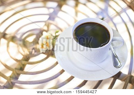 Sunny morning coffee in white cup on the table with glass in the garden. Natural light. Good morning mood. Flowers on the table.