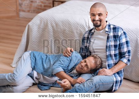 So nice to be close to you. Delighted positive smiling non-traditional couple sitting on the floor in the bedroom and watching television while hugging and switching the channel