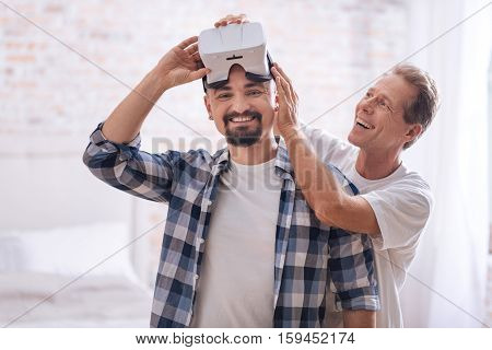 We spending enjoyably our free time. Smiling cheerful delighted non-traditional couple standing at home and testing virtual reality glasses while expressing happiness and interest