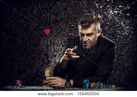 Excited gambling man throwing chips on a game table in a casino. Gambling, playing cards and roulette.