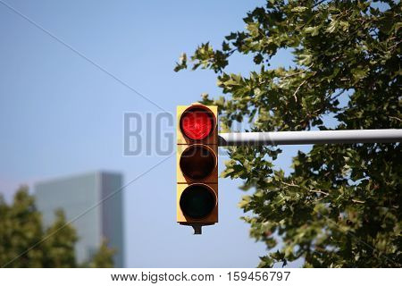 Red traffic light on the background of blue sky