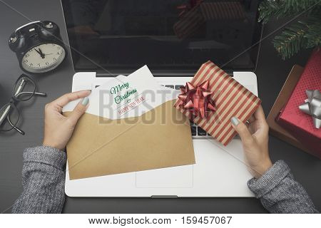 business woman hand holding christmas card and gift box on desk office concept office christmas and happy new year.