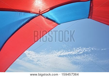Look from red - blue beach tent in the blue sky
