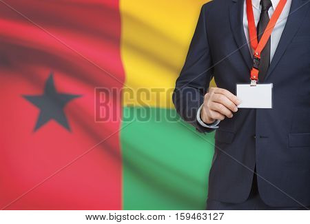 Businessman Holding Name Card Badge On A Lanyard With A National Flag On Background - Guinea-bissau