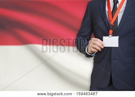 Businessman Holding Name Card Badge On A Lanyard With A National Flag On Background - Indonesia