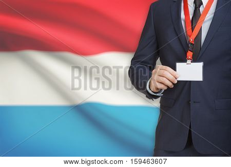 Businessman Holding Name Card Badge On A Lanyard With A National Flag On Background - Luxembourg