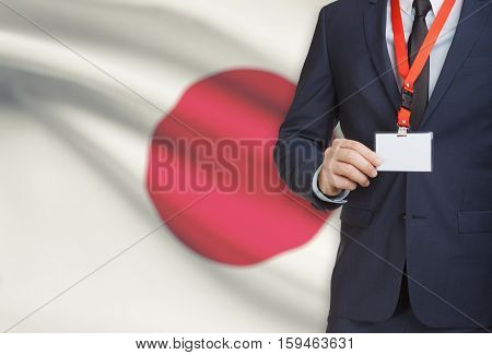 Businessman Holding Name Card Badge On A Lanyard With A National Flag On Background - Japan