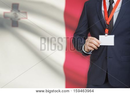 Businessman Holding Name Card Badge On A Lanyard With A National Flag On Background - Malta