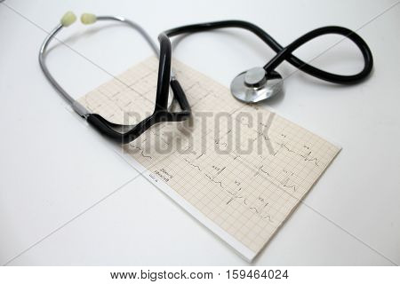 Stethoscope and electrocardiogram printed on a gray background.